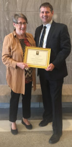 Sally Gant receives the Certificate of Merit from Board member Justin Stelter.
